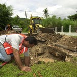 In this 2003 file photo, Guam Waterworks Authority's Pete Arceo, left, fixes a leak in a service line in Santa Rita as Jess Lujan watches.