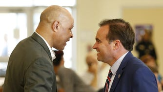 City Manager Harry Black and Mayor John Cranley shake hands before a community meeting to discuss the future of the city's Collaborative Agreement at Taft High School in the West End neighborhood of Cincinnati on Tuesday, Sept. 26, 2017.
