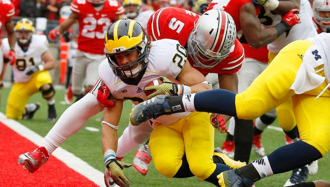 Michigan Wolverines running back Drake Johnson (20) plunges in for a touchdown past Ohio State Buckeyes linebacker Raekwon McMillan.