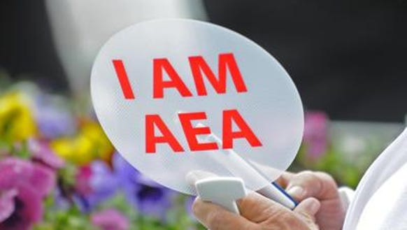 An AEA member holds a fan at a rally supporting education