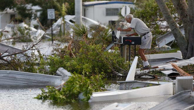 Richard Norwak retrieves a letter from his mailbox a day after Hurricane Irma made landfall in the Holiday Manor area of Naples, Fla..