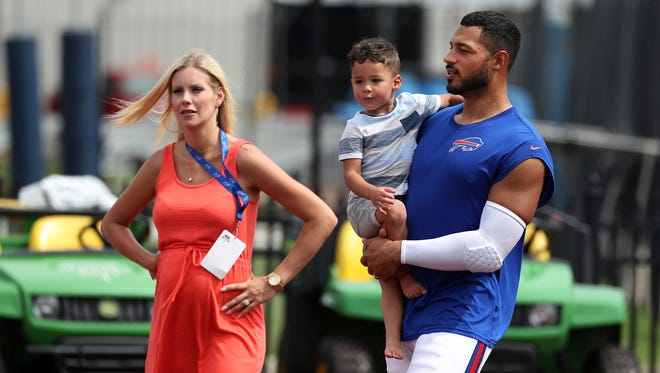 Bills tight end Logan Thomas holding his son Logan, 2, and chatting with his wife Brandie after practice. She brings their four boys to training camp every day. The Thomas' are expecting their fifth boy later this year.