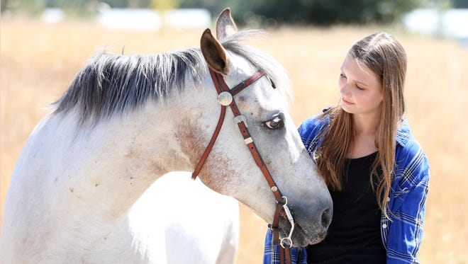 Elisabeth Burleson, 15, of Keizer rides her horse, Suzie, a 16-year-old Quarter Horse/POA mix on Friday, Aug. 5, 2016, at the Keizer Equestrian Center. Burleson recently competed in the Extreme Mustang Makeover and trained a 17-month-old mustang named Delilah.