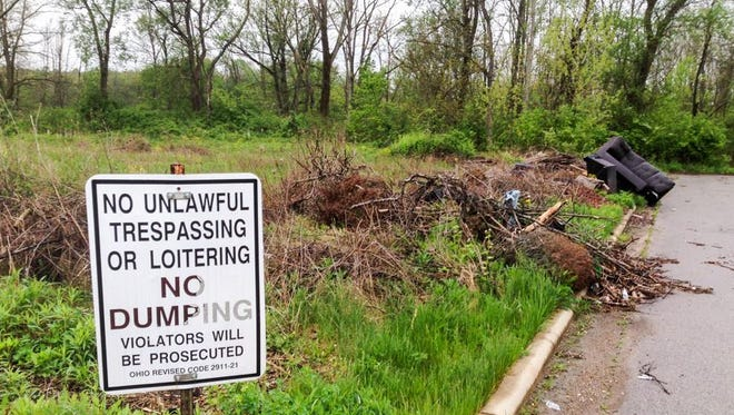 Mansfield police have arrested two people on misdemeanor charges of illegal dumping on Brushwood Drive off South Main Street.