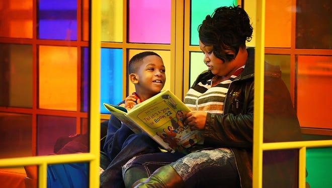 The future of public art in Memphis is looking up with UrbanArt Commission celebrating 20 years. Fonda Lyles reads to her son Noah Lyles, 8, inside of the Reading Room by Nancy Cheairs, a one of several UrbanArt pieces at the Hooks Central Library.