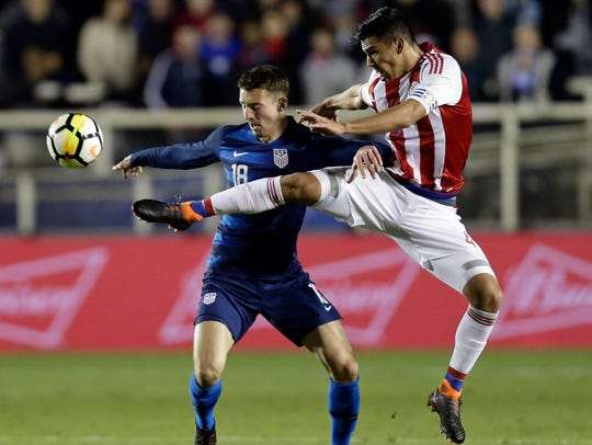 The United States' Andrija Novakovich (18), a Muskego native, battles Paraguay's Fabian Balbuena during the second half of an international friendly soccer match on March 27 in Cary, North Carolina. The United States won 1-0. (AP Photo/Gerry Broome)