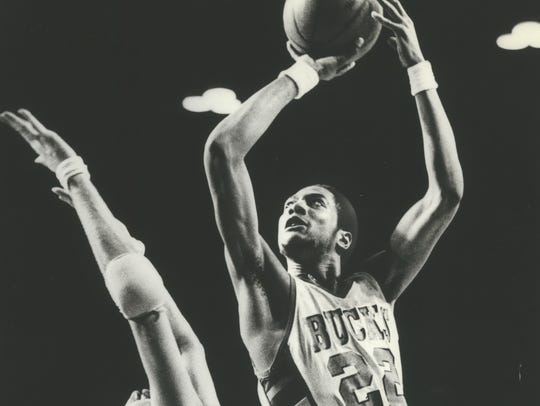 Alex English of the Bucks leaned into Tom McMillen