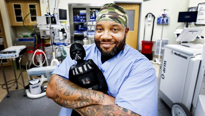 "Darthvader Williamson, holds a crochet doll of his namesake character from the ""Star Wars"" movies inside an operating room at St. Francis Hospital-Bartlett  in suburban Memphis were his is a surgical technician."