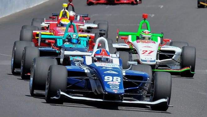 Colton Herta (98) leads a groups of cars going into turn one during the Freedom 100 IndyLights race during Carb Day at the Indianapolis Motor Speedway on Friday, May 25, 2018.