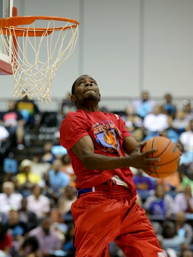 """Ivory Cobb goes up for a reverse dunk during the slam dunk contest before the Amp Harris & Reggie Wayne """"Saving Our Youth"""" Celebrity Basketball  Game inside the Indiana Convention Center, Saturday, July 19, 2014, in Indianapolis."""