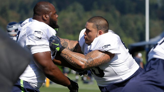 Seattle Seahawks' Jesse Williams, right, pushes Ahtyba Rubin in a drill at an NFL football training camp Thursday, Aug. 6, 2015, in Renton, Wash.