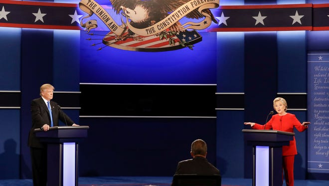 Democratic presidential nominee Hillary Clinton answers a question as Republican presidential nominee Donald Trump listens during the presidential debate at Hofstra University in Hempstead, N.Y., Monday, Sept. 26, 2016.