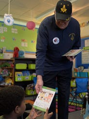 Wayne Lodge member Sam Fite gives a book to a first-grader