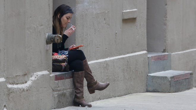 A woman has a cigarette while using a smart phone, Thursday, March 10, 2016, in Sacramento, Calif.
