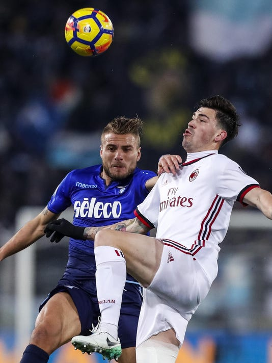 Lazio's Ciro Immobile, left, and AC Milan's Alessio Romagnoli vie for the ball during the Italian Cup, second-leg semifinal soccer match between Lazio and AC Milan, at the Rome Olympic stadium Wednesday, Feb. 28, 2018. (Angelo Carconi/ANSA via AP)