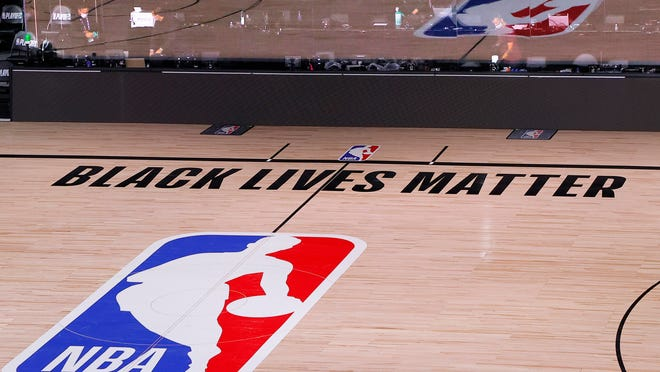 An empty court and bench are shown with no signage following the scheduled start time in Game 5 of an NBA basketball first-round playoff series, Wednesday, Aug. 26, 2020, in Lake Buena Vista, Fla. NBA players made their strongest statement yet against racial injustice Wednesday when the Milwaukee Bucks didn't take the floor for their playoff game against the Orlando Magic.