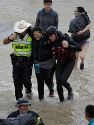 A woman is helped by rescue personnel while being evacuated