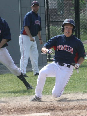 Franklin's Tyler Camp slides home with the Patriots' second run as Ryan Prohaska and head coach Matt Fournier look on.