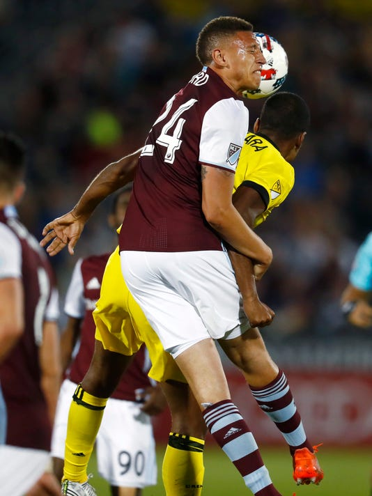 FILE - In this June 3, 2017, file photo, Colorado Rapids defender Kortne Ford, front, heads the ball over Columbus Crew forward Ola Kamara in the second half of an MLS soccer game in Commerce City, Colo. Ford's mother, Laurie, is battling breast cancer that has spread to her bones, which has prompted players to plan an auction of their jerseys after the team's game against Seattle on Tuesday, July 4, 2017, to raise money for her treatment. (AP Photo/David Zalubowski, file)