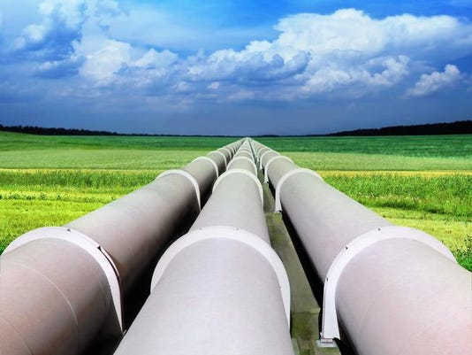 Three gas pipelines in a green field with blue sky