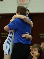 Centerville's Javon Phillips hugs his father and coach