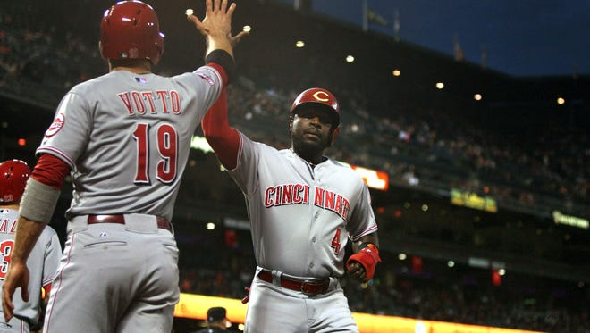 Reds first baseman Joey Votto (19) greets second baseman Brandon Phillips (4) after he scored on a two-run triple by shortstop Ivan De Jesus Jr. (not pictured) in the first inning against the San Francisco Giants at AT&T Park.