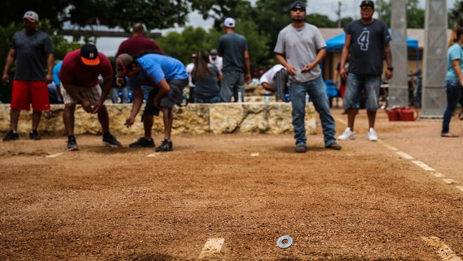 Participants compete in a washer-pitching tournament during The Bosque summer grand opening Saturday, June 3, 2017.