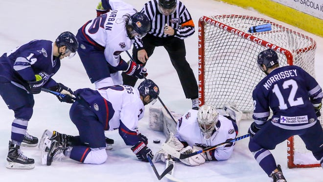Pensacola's Trever Hertz (14) and Shayne Morrissey (12) battle to get the puck in the goal against Macon goaltender Charlie Finn at the Pensacola Bay Center on Sunday, January 14, 2018. Though Macon won the game 4-2, the Ice Flyers have won three of their last five games and stay in first place with 43 points.