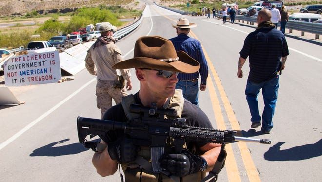 Cliven Bundy (center rear) walks away from a news conference under security by militia in Bunkerville, Nevada April 14, 2014. In front is Darin Stanley from St. George, Utah. The BLM seized about 400 head of cattle from the 68-year-old rancher over his refusal to pay an estimated $1 million in grazing fees over 20 years. They have since backed down and returned his cattle.
