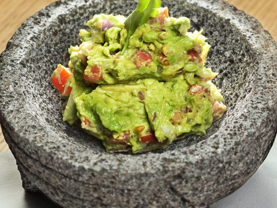 Guacamole made tableside is served in lava rock vessels