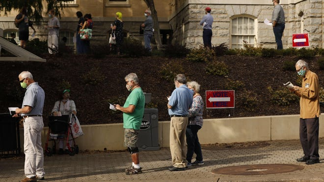 Early voters wait in line Wednesday to cast ballots at the Board of Elections office in downtown Athens and nearby City Hall.