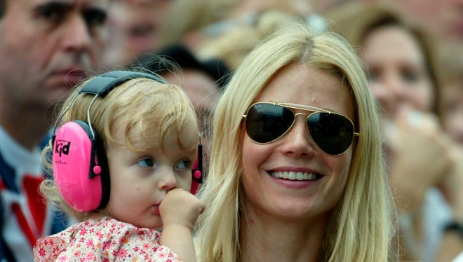 Gwyneth Paltrow, holding her daughter Apple Martin, watches her husband Chris Martin perform on stage with his band Coldplay at the Live 8 concert in Hyde Park, London, July 2, 2005.