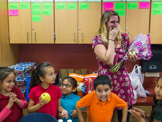 Ashley Heirls, surrounded by her students, is awarded a Golden Apple award at Highlands Elementary School on Tuesday, Feb. 14, 2017. Every year Champions for Learning gives out the awards for best teaching practices.