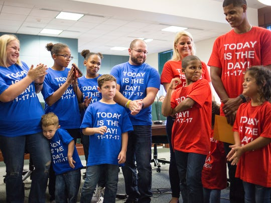 A crowded courtroom filled with applause as judge Joseph G. Foster made official Luis and Jessica Buther's adoption of 9-year-old Elijah, in red on right, at the Collier County Courthouse on Friday, Nov. 17, 2017.