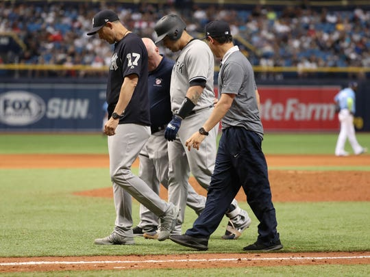 New York Yankees catcher Gary Sanchez (24) walks off the field with manager Aaron Boone (17).
