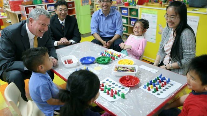 New York City Mayor Bill de Blasio, left, and City Council member Carlos Menchaca, third from left, visit a prekindergarten class May 27, 2014, at the Brooklyn Chinese American Association Early Childhood Education Center in Sunset Park, in the Brooklyn borough of New York.