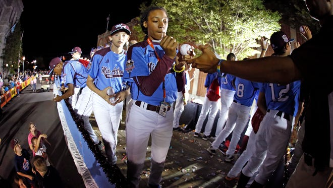 Mo'ne Davis, center, a member of the Taney Little League team from Philadelphia, signs baseballs as she and her teammates ride in the Little League Grand Slam Parade as it makes its way through downtown Williamsport, Pa., Wednesday. Davis is one of two girls competing in the Little League World Series tournament this year.