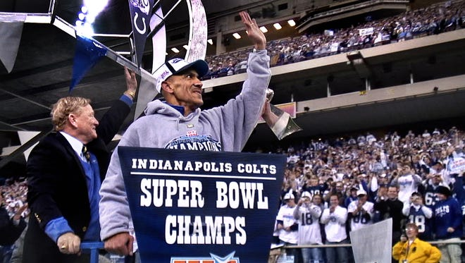 Tony Dungy, center, the first black coach to win the Super Bowl, acknowledges the cheers of Indianapolis Colts fans, along with Colts President Bill Polian (cq), left, as they enter a rally in the RCA Dome following a parade through Downtown Indianapolis on Monday, February 5, 2007. Thousands of fans turned out in bitterly cold weather for the celebration the day after the Colts won their first Super Bowl since coming to Indianapolis, beating the Chicago Bears 29-17 in Super Bowl XLI.