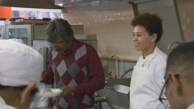"""Celebrity chef Marcus Samuelsson, left, tastes a dish for an episode of """"Undercover Boss,"""" filmed in at Monroe College's New Rochelle campus."""