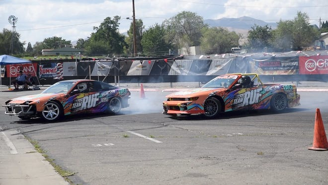 Two cars speed around the track, skidding and sliding around tight curves at the Livestock Event Center during Hot August Nights drift event, Aug. 10.