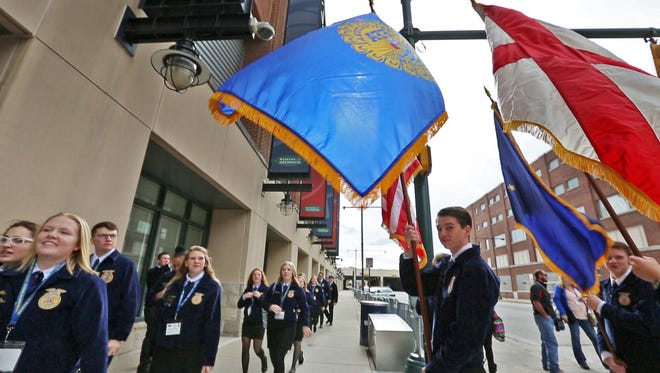 Walking under the FFA and other flags, FFA members head to the Fieldhouse after the FFA Grand March down FFA Way (Georgia St.) to Bankers Life Fieldhouse for the official opening of the 90th National FFA Convention, Wednesday, Oct. 25, 2017.