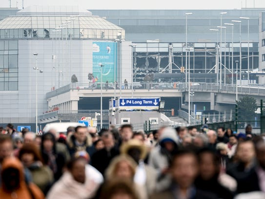 Passengers evacuate the Brussels Airport, in Zaventem,