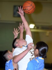 Navajo Prep's Tyler Pete fights for a rebound against Dulce on Friday at the Eagles Nest in Farmington.