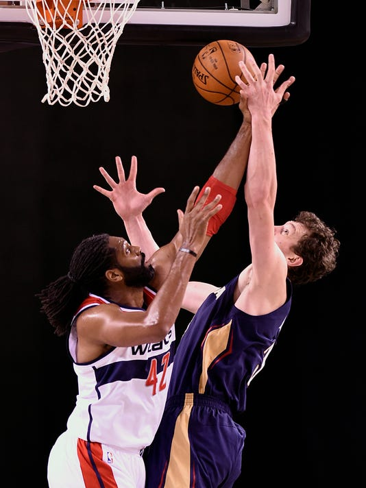 Washington Wizards' Nene, left, and New Orleans Pelicans' Omer Asik go after a rebound in the first half of a pre-season NBA basketball game  Monday, Oct. 20, 2014 in Baltimore.(AP Photo/Gail Burton)