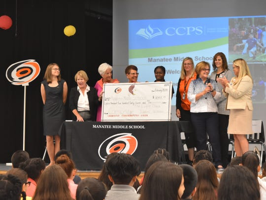 Eagle Creek Women's Golf Association members present a check of more than $18,000 to Manatee Middle School students on March 1, 2017. The money will go toward purchasing 60 laptops for students to take home.