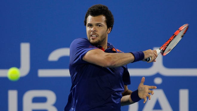 Jo-Wilfried Tsonga of France returns the ball to Andy Murray of Britain during the first day of the Mubadala World Tennis Championship in Abu Dhabi, United Arab Emirates, on Dec. 26, 2013.