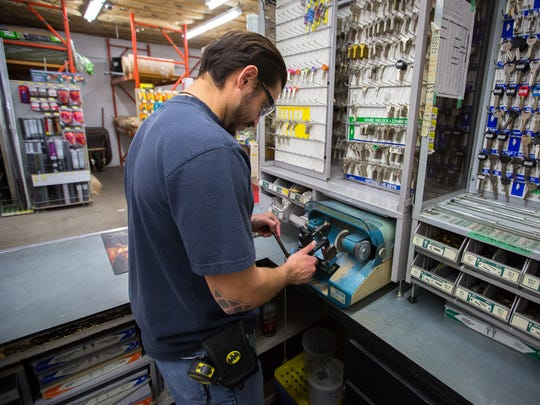 Ian Lujan, who's worked at Hayden's Hardware for 6 months, makes a key in the service area of the store.
