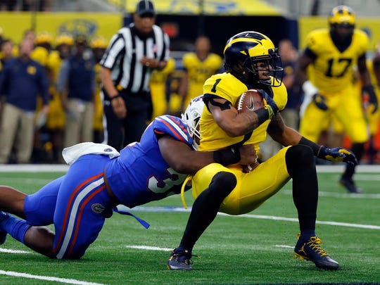 Florida linebacker David Reese (33) stops Michigan wide receiver Kekoa Crawford (1) from gaining extra yardage after Crawford made a catch in the first half of an NCAA college football game, Saturday, Sept. 2, 2017, in Arlington, Texas. (AP Photo/Tony Gutierrez)