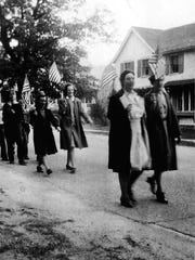 Two Richmond High School teachers lead a parade of students through Richmond village on May 8, 1945, to celebrate the end of the war in Europe.