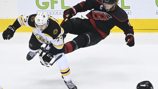 Boston Bruins defenseman Charlie McAvoy (left) crashes into Carolina Hurricanes center Jordan Staal during the third period of an NHL Eastern Conference Stanley Cup playoff game in Toronto on Monday.